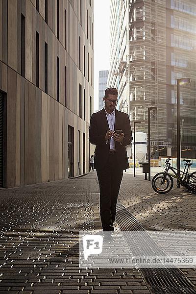 Geschäftsmann geht in der Stadt spazieren und überprüft Handy