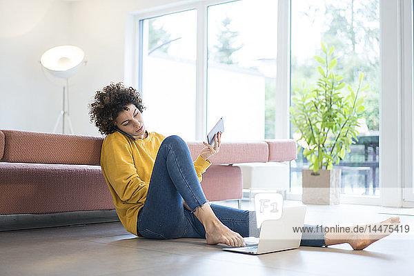 Frau benutzt Laptop  Handy und Tablet zu Hause