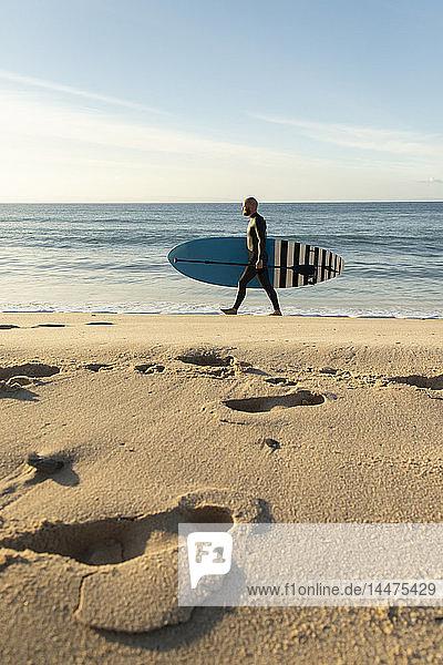 Spanien  Andalusien  Tarifa  Mann geht mit aufrechtem Paddelbrett am Strand
