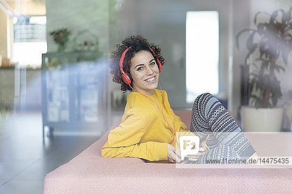 Glückliche Frau  die zu Hause auf der Couch Musik hört