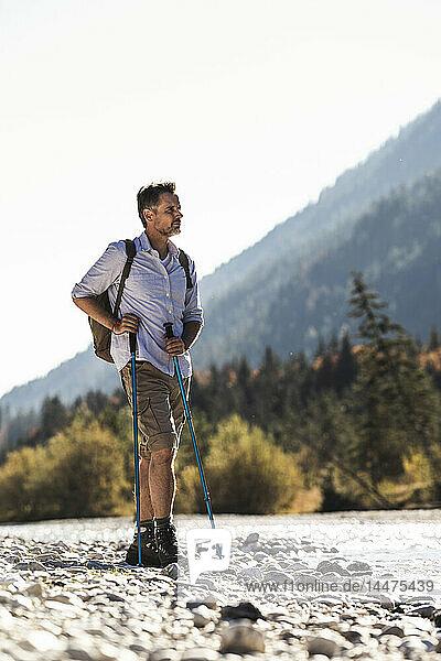 Österreich  Alpen  Mann auf einer Wanderung auf Kieselsteinen an einem Bach stehend
