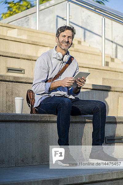 Porträt eines lächelnden  reifen Mannes auf einer Treppe sitzend mit Tablette