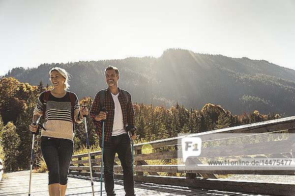 Österreich,  Alpen,  glückliches Paar auf einer Wanderung über eine Brücke