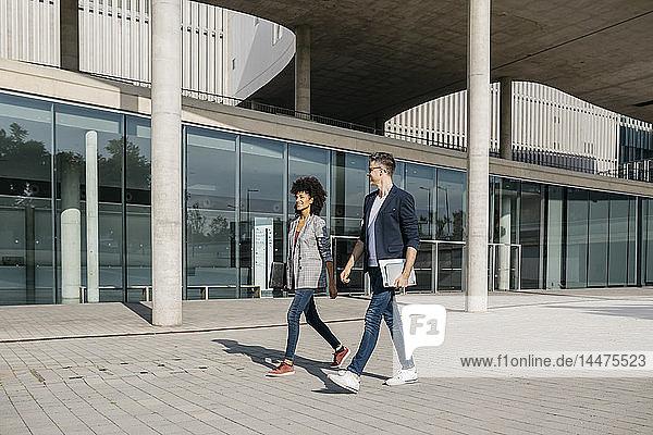 Zwei Kollegen gehen vor dem Bürogebäude