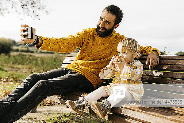 Father and daughter sitting on a bench in the park in autumn  father taking a selfie  daughter eating an apple