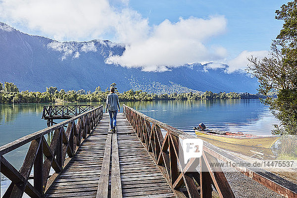 Chile  Chaiten  Lago Rosselot  woman walking on jetty