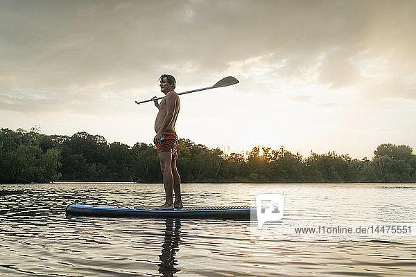 Mann steht auf einem SUP-Brett auf einem See bei Sonnenuntergang