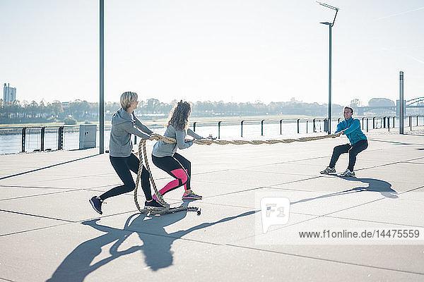Freunde trainieren am Flussufer  am Seil ziehen