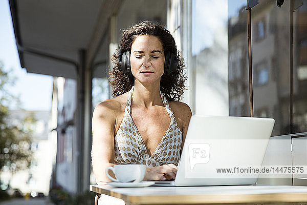 Reife Frau sitzt im Café  trägt Kopfhörer  benutzt Laptop