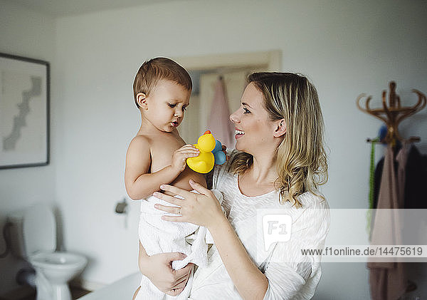 Smiling mother holding toddler son in bathroom at home