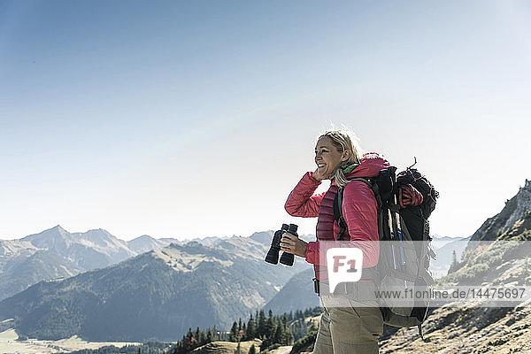 Österreich  Tirol  lächelnde Frau mit Fernglas auf einer Wanderung