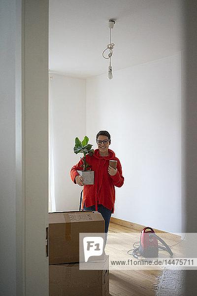 Junge Frau zieht in ihr neues Zuhause ein und trägt eine Topfpflanze