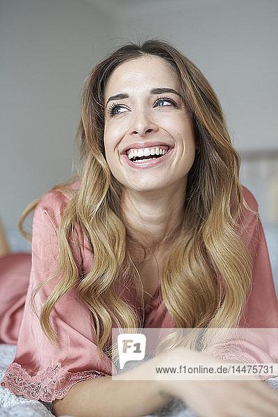Lachende junge Frau im Bademantel im Bett liegend