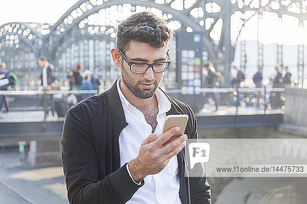 Deutschland  München  junger Geschäftsmann betrachtet Handy am zentralen Busbahnhof
