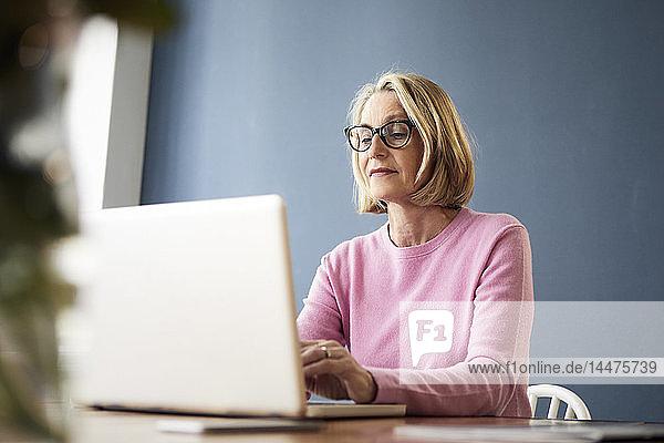 Reife Frau benutzt Laptop zu Hause