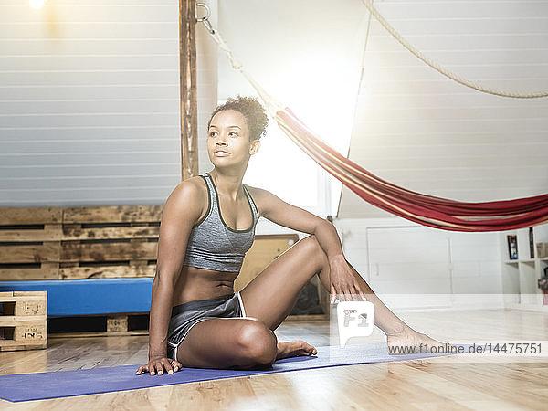 Junge Frau sitzt auf Yogamatte und macht eine Pause