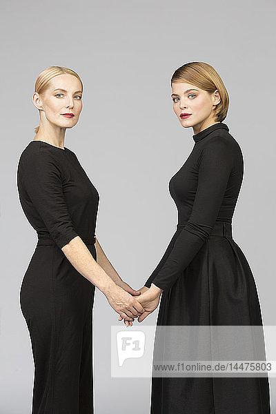 Studioporträt einer Mutter und einer erwachsenen Tochter  die Händchen halten