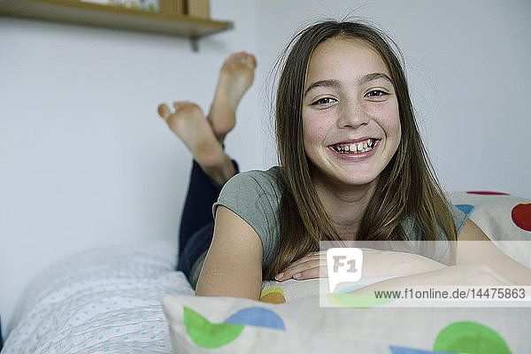 Portrait of laughing girl lying on bed