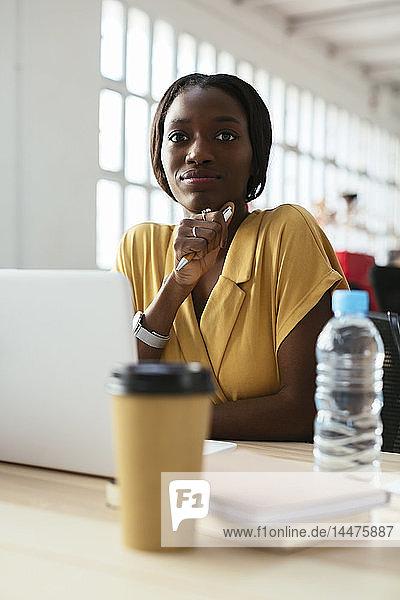 Porträt einer selbstbewussten jungen Frau am Schreibtisch im Büro