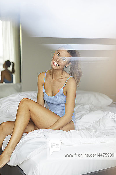 Porträt einer glücklichen jungen Frau auf dem Bett sitzend