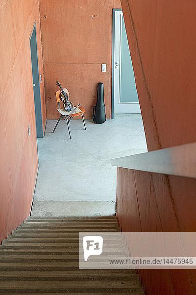 Geige  Bogen  Noten auf Holzstuhl und an die Wand gelehnter Geigenkasten