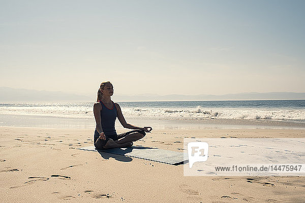 Young woman exercising yoga at a beach