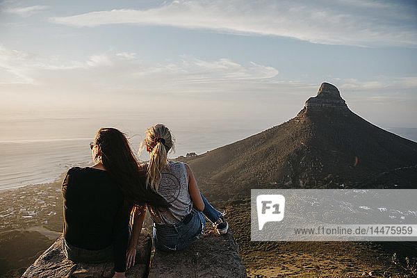 Südafrika  Kapstadt  Kloof Nek  zwei Frauen sitzen bei Sonnenuntergang auf einem Felsen