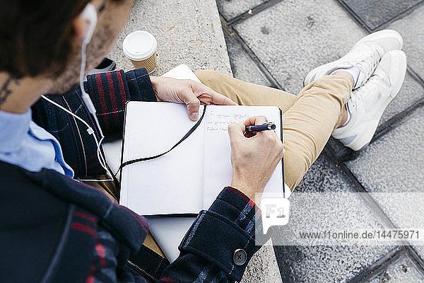 Man sitting outside taking notes