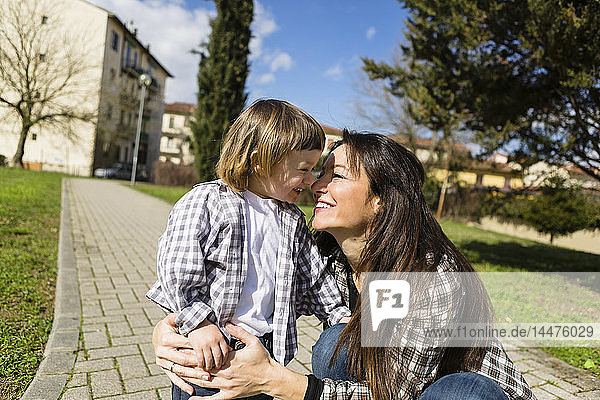 Mother cuddling happy toddler son on a path