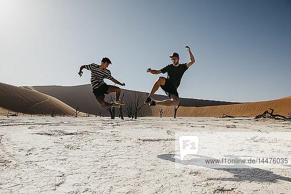 Namibia  Namib-Wüste  Namib-Naukluft-Nationalpark  Sossusvlei  zwei Männer springen in Deadvlei