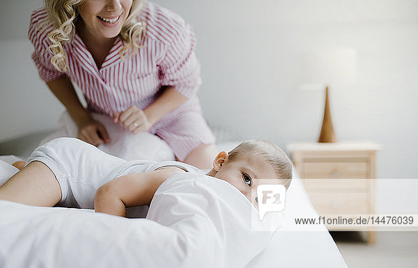 Smiling mother and toddler son in bed at home