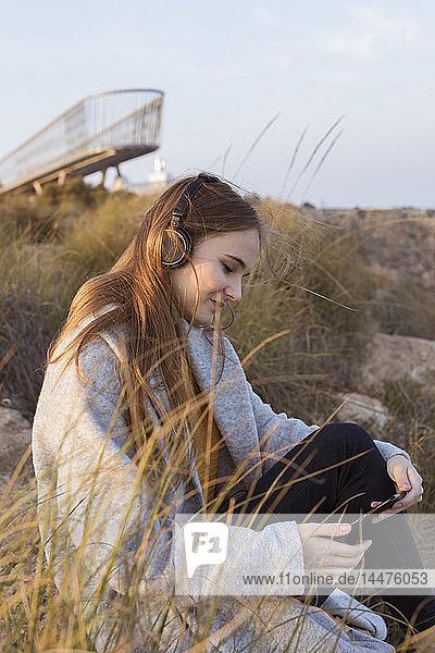 Spanien  Alicante  Santa Pola  Kap Santa Pola  junge Frau sitzt bei Sonnenuntergang auf einem Felsen und hört Musik auf ihrem Handy
