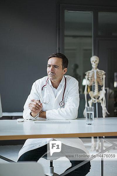 Am Schreibtisch sitzender Arzt in medizinischer Praxis mit Skelett im Hintergrund
