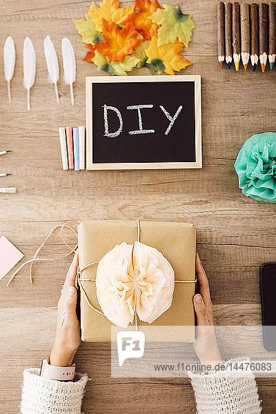 Draufsicht einer jungen Frau  die in ihrem Atelier ein verpacktes Geschenk zeigt