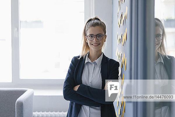 Porträt einer selbstbewussten jungen Geschäftsfrau  im Amt stehend