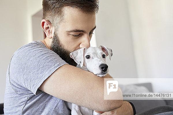 Mann kuschelt zu Hause mit seinem Hund