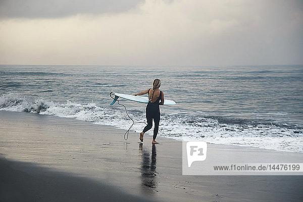 Indonesien  Bali  Strand von Canggu  Surfer mit Surfbrett am Strand