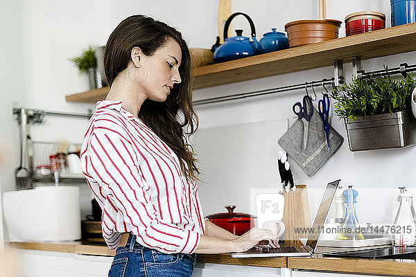 Woman using laptop in kitchen at home