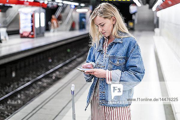 Spanien  Barcelona  junge blonde Frau steht am U-Bahn-Bahnsteig und schaut auf ihr Handy