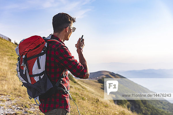 Italien  Monte Nerone  Wanderer auf dem Gipfel eines Berges im Gespräch mit einem Walkie-Talkie