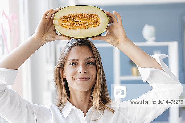 Junge Frau balanciert eine halbe Melone auf ihrem Kopf
