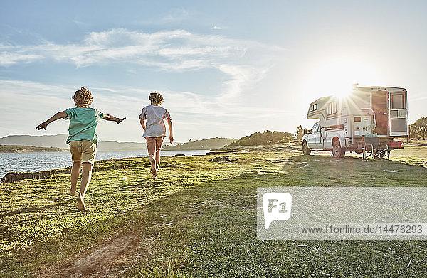 Chile  Talca  Rio Maule  zwei Jungen laufen auf der Wiese neben dem Wohnmobil am See