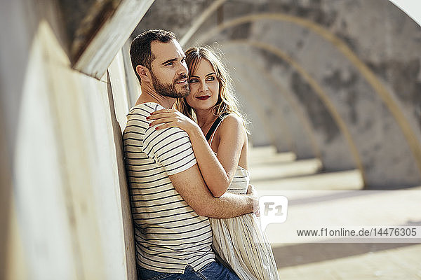Spain  Andalusia  Malaga  affectionate tourist couple hugging under an archway in the city