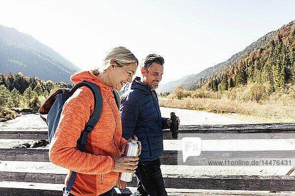Österreich  Alpen  glückliches Paar auf einer Wanderung über eine Brücke
