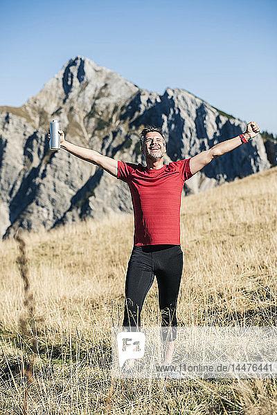 Österreich  Tirol  glücklicher Athlet auf der Alm stehend