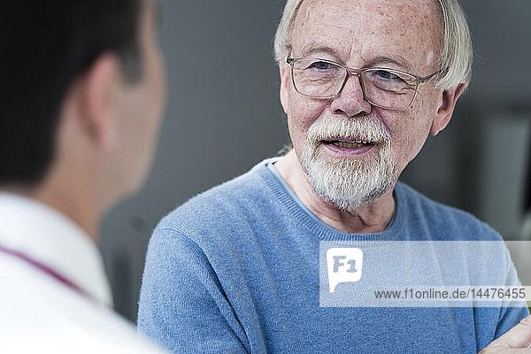 Älterer Patient im Gespräch mit Arzt in der medizinischen Praxis
