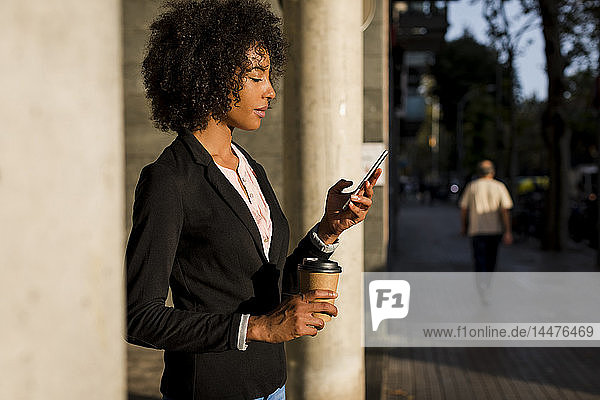 Businesswoman with coffee to go looking at cell phone at evening twilight