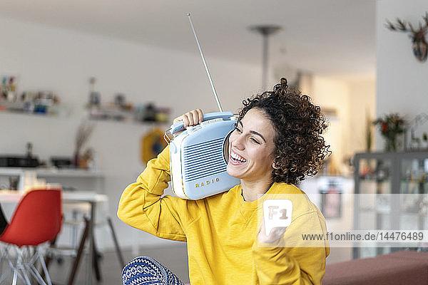 Sorglose Frau  die zu Hause mit einem tragbaren Radio Musik hört