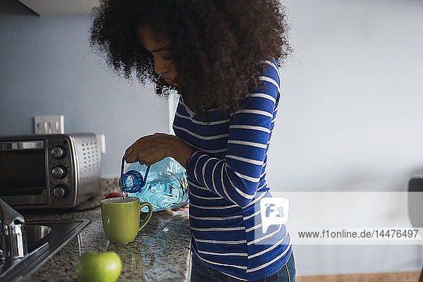 Young woman pouring water into a mug in her kitchen
