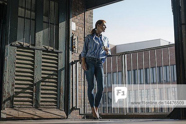 Deutschland  Hamburg  Speicherstadt  Geschäftsfrau mit Tasse Kaffee am Fenster stehend mit Blick auf die Stadt